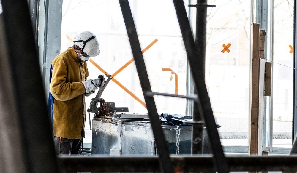 Homem na fábrica com equipamento de proteção
