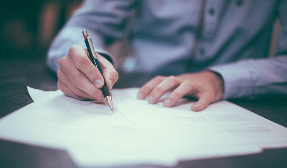 Homem escrevendo em um papel